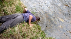 Tony Vorster dunks his head in St. Louis Creek at the Fraser Experimental Forest during a break from sampling.