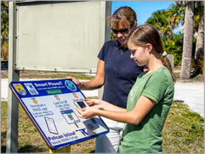 Visitors at Pelican Island National Wildlife Refuge in Florida scan QR code enabled signs to learn more. Credit: Vince Lamb.
